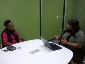 Kia Stearn engages in a lively peer coaching session with a client working on her budget. Combining her income with community resources helps the client reach her goal of financial stability.